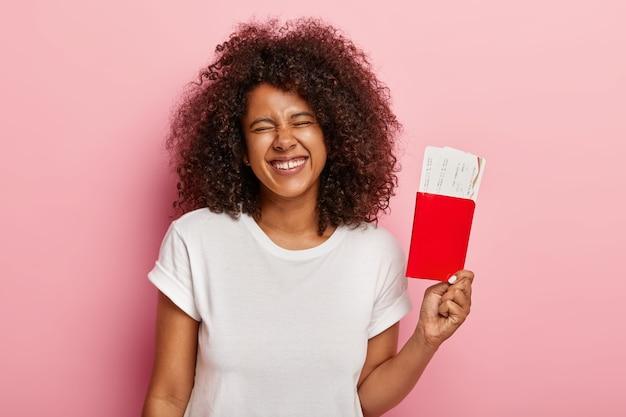 즐거운 여성 관광객은 여행 전에 재미 있고, 여권에 탑승권을 들고, 항해에 대해 흥분하고, 긍정적으로 웃으며, 캐주얼 한 복장을 입고, 분홍색 벽에 고립되고, 비행을 기다립니다. 무료 사진