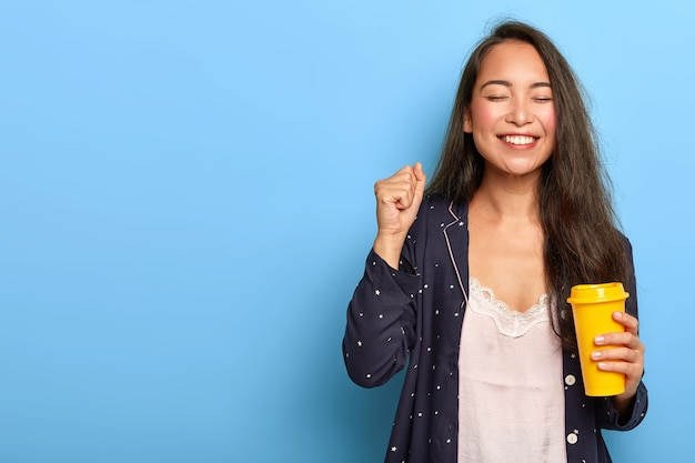 Joyous happy asian woman with long dark hair, enjoys morning coffee, clenches fist, dressed in nightwear, smiles broadly Free Photo