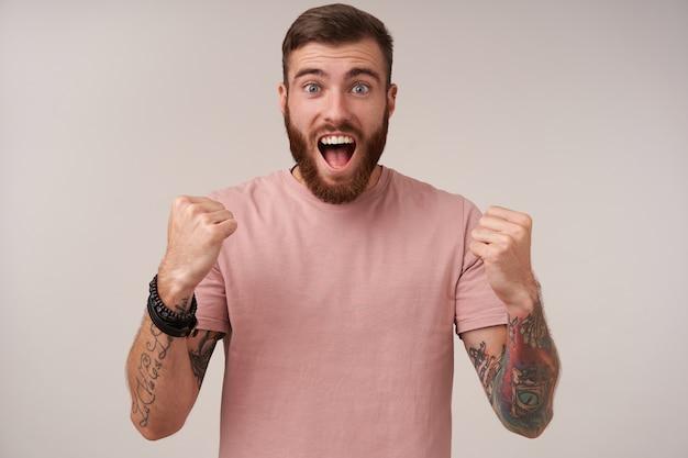 Радостный симпатичный голубоглазый бородатый мужчина с татуировками радуется забитому голу с широко открытым ртом и круглыми глазами, изолированные на белом Бесплатные Фотографии