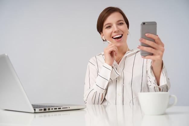 Gioiosa giovane donna bruna dai capelli corti con acconciatura casual tenendo il cellulare in mano alzata e avendo videochiamata, sorridendo felicemente mentre è seduto su bianco Foto Gratuite