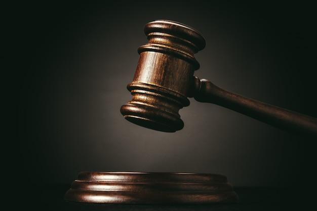 Judge (auction) gavel on a black wall Premium Photo