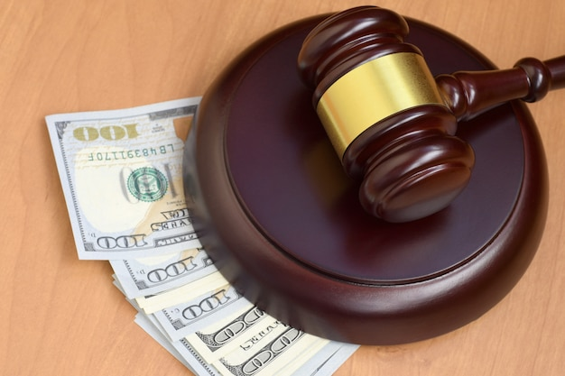 Молоток судьи и деньги на коричневом деревянном столе Premium Фотографии