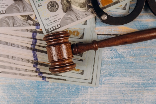 Judge gavel and money on of metal police handcuffs blue wooden table. Premium Photo