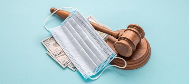 Молоток судьи с медицинской маской и деньгами на синем фоне коррупция в концепции медицинской области Premium Фотографии