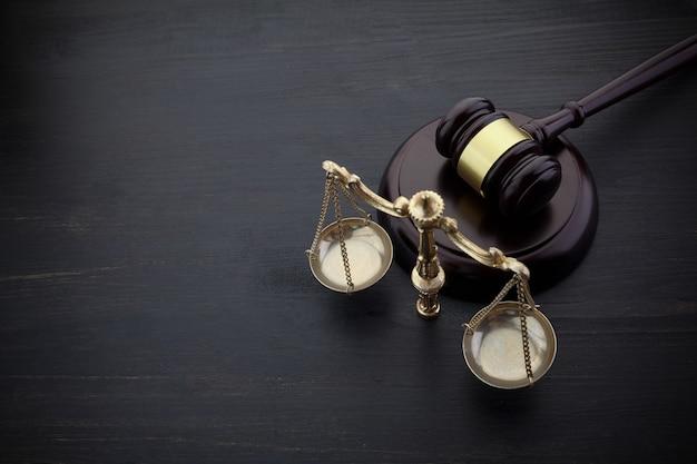 Судьи молоток и весы правосудия на черном столе Premium Фотографии