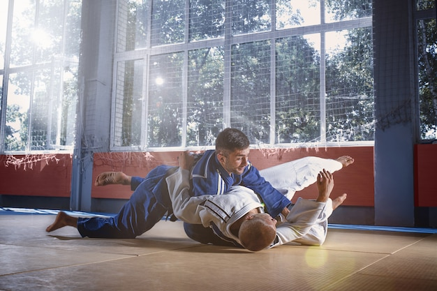 Judo fighters showing technical skill while practicing martial arts in a fight club Free Photo