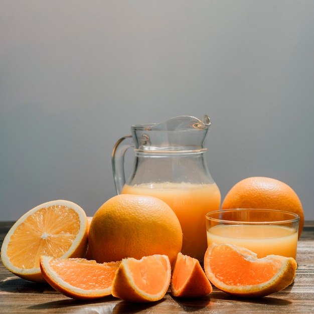 Jug of delicious orange juice surrounded by glasses and oranges Free Photo