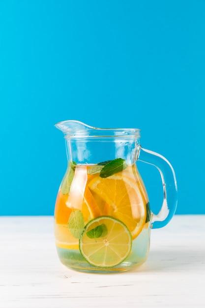 Brocca con limonata fatta in casa con sfondo blu Foto Gratuite