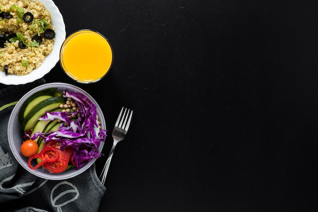Juice; chia seed pudding and fresh vegetables salad on black background Free Photo