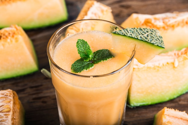 The juice of melon with mint in a glass jar on the table.hami melon Premium Photo
