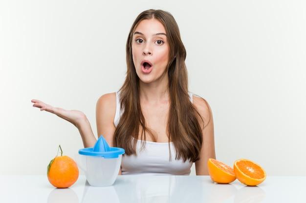 Молодая кавказская женщина с оранжевым juicer впечатлила держащ экземпляр на ладони. Premium Фотографии