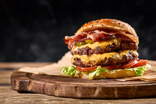 Juicy american burger, hamburger or cheeseburger with two beef patties, with sauce and basked on a black space Premium Photo