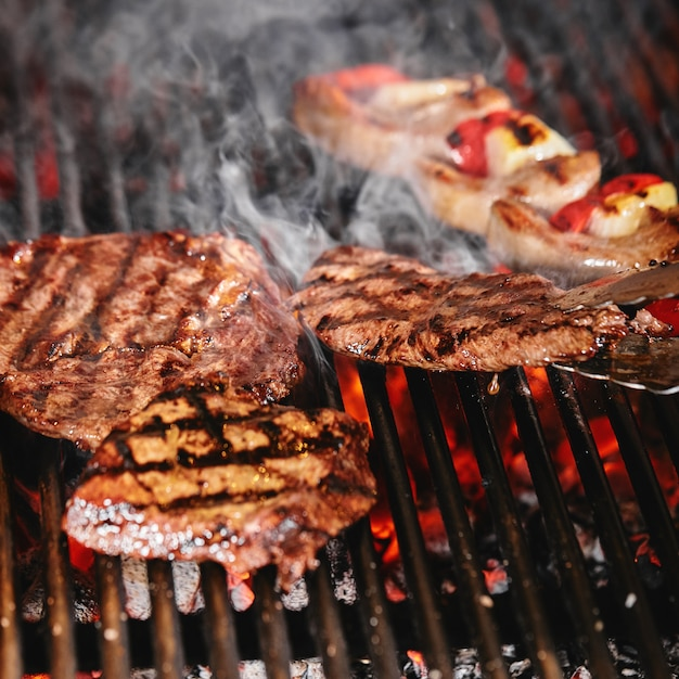 Juicy beef steak flips in a barbecue flame, life style, food photo, copy space Premium Photo