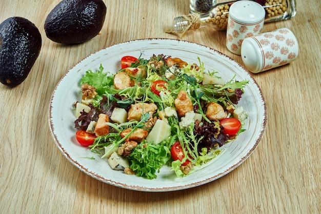 木製のテーブルの青いボウルにロックフォールチーズ、ブルーチーズレタス、ゴマ、アボカドと照り焼きチキンとチェリートマトのジューシーなグリーンサラダ。健康食品。フィットネス栄養 Premium写真