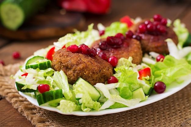 크랜베리 소스와 소박한 스타일의 나무 테이블에 샐러드와 육즙 고기 Cutlets. 무료 사진