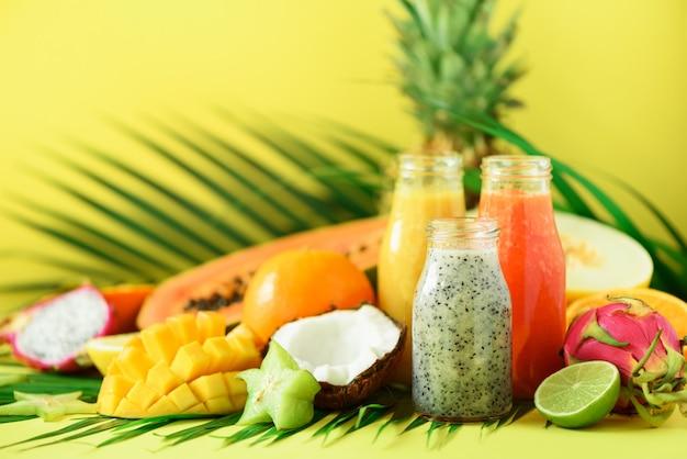 Juicy papaya and pineapple, mango, orange fruit smoothie in jars on yellow background. detox, summer diet food, vegan concept. Premium Photo