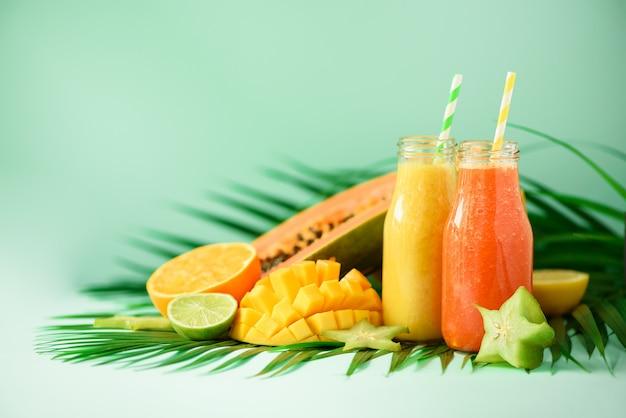 Juicy papaya and pineapple, mango, orange fruit smoothie in two jars. detox, summer diet food, vegan concept. fresh juice in glass bottles Premium Photo