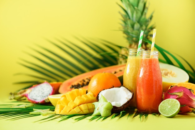 Juicy papaya and pineapple, mango, orange fruit smoothie in two jars. detox, summer diet food, vegan concept. Premium Photo