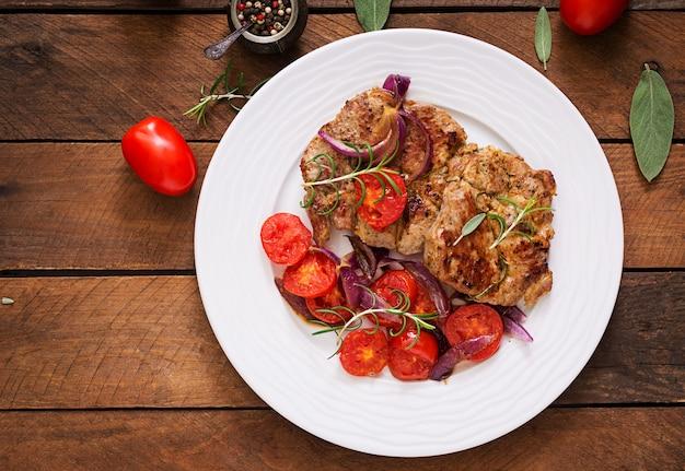 Сочный стейк из свинины с розмарином и помидорами на белой тарелке Бесплатные Фотографии