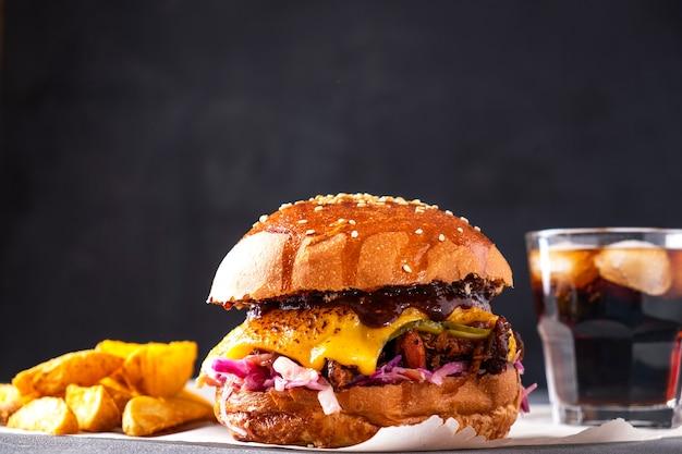 프렌치 프라이와 소다를 곁들인 육즙 풀드 포크 버거. 길거리 음식 프리미엄 사진
