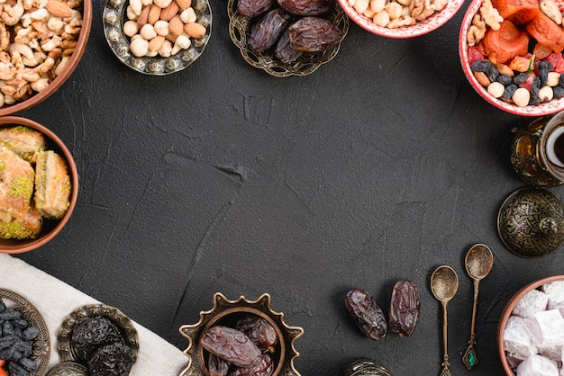 Juicy ripe dates; nuts; lukum and baklava on black concrete backdrop Free Photo
