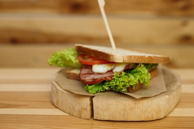 Juicy sandwich with grilled bread and bacon wait for you on wooden plate Premium Photo