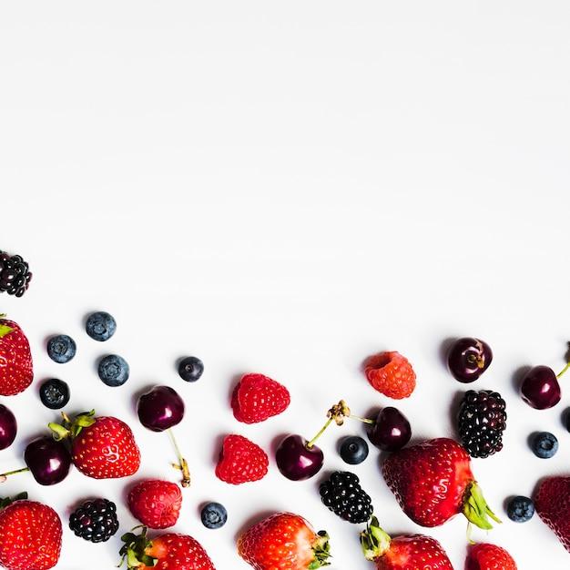Juicy seasonal berries on light surface Free Photo