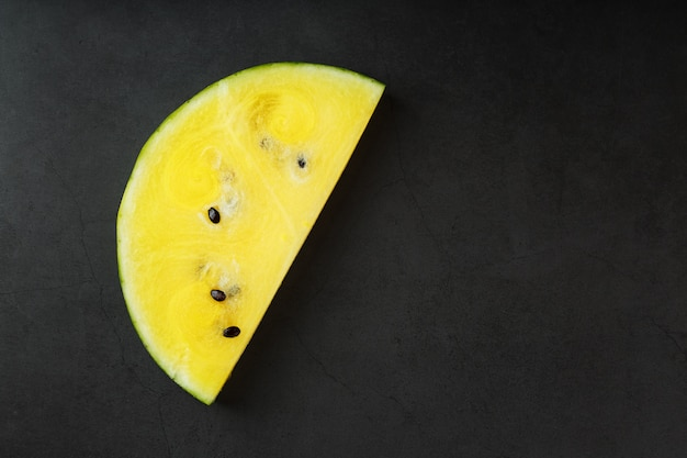Juicy slice of yellow watermelon on stone black Premium Photo
