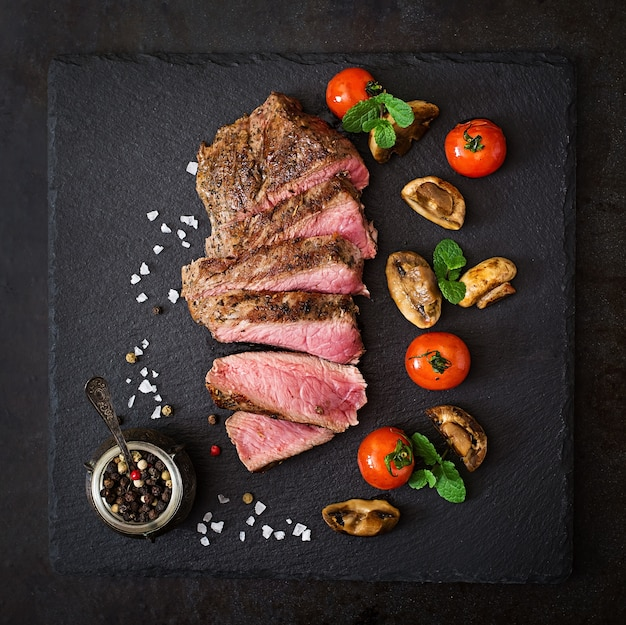 Juicy steak medium rare beef with spices and grilled vegetables. top view Premium Photo
