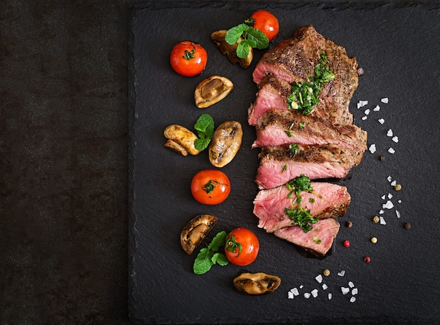 Juicy steak medium rare beef with spices and grilled vegetables. Free Photo