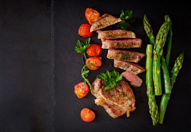 Juicy steak medium rare beef with spices and tomatoes, asparagus. Free Photo