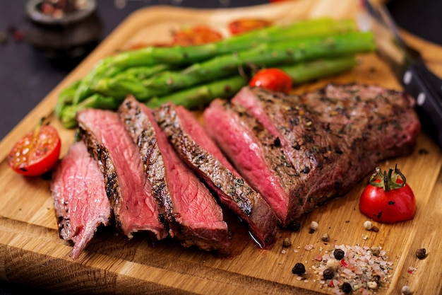 Juicy steak rare beef with spices on a wooden board and garnish of asparagus. Premium Photo