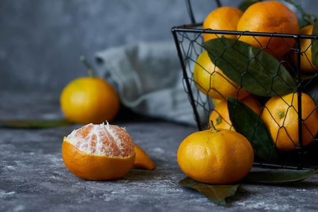 Juicy tangerines with leaves in a basket Premium Photo