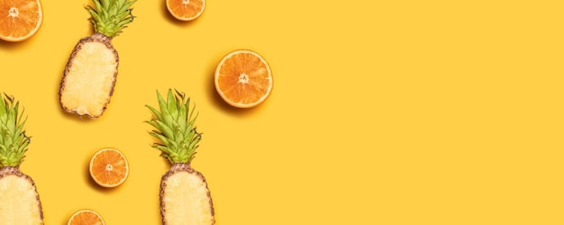 Juicy tropical fruits on a yellow background: oranges, coconuts, lemons, pineapples. Premium Photo