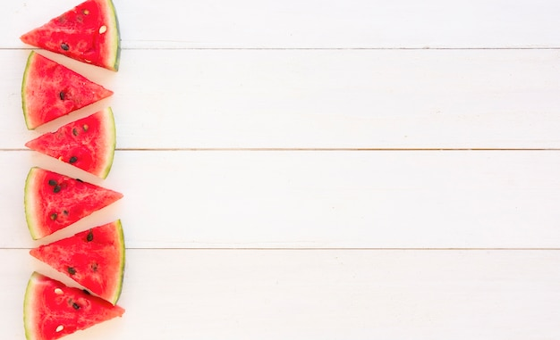 Juicy watermelon slices design on wooden white plank backdrop Free Photo