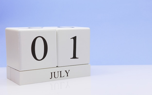 July 01st. day 1 of month, daily calendar on white table with reflection, with light blue background. Premium Photo