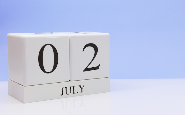 July 02st. day 2 of month, daily calendar on white table with reflection, with light blue background. Premium Photo