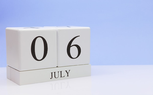July 06st. day 6 of month, daily calendar on white table with reflection, with light blue background. Premium Photo