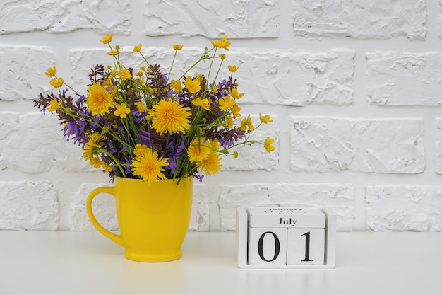 July 1 and yellow cup with bright colored flowers against white brick wall. Premium Photo