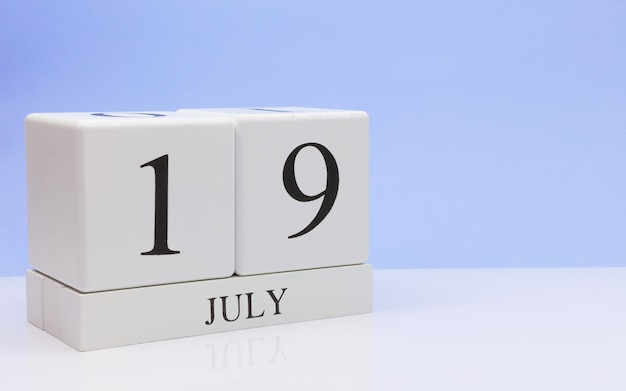 July 19st. day 19 of month, daily calendar on white table with reflection, with light blue background. Premium Photo