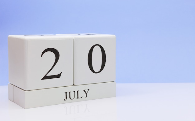 July 20st. day 20 of month, daily calendar on white table with reflection, with light blue background. Premium Photo