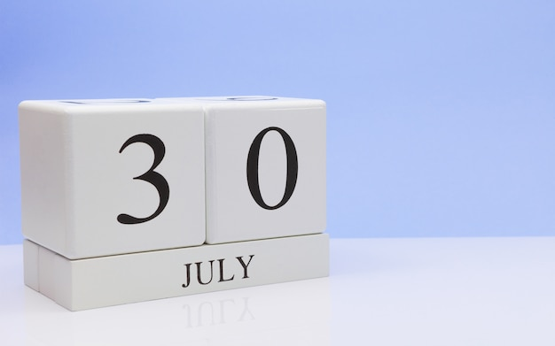 July 30st. day 30 of month, daily calendar on white table with reflection, with light blue background. Premium Photo