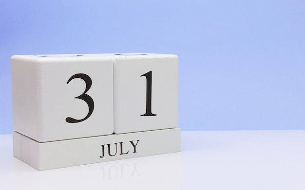 July 31st. day 31 of month, daily calendar on white table with reflection, with light blue background. Premium Photo