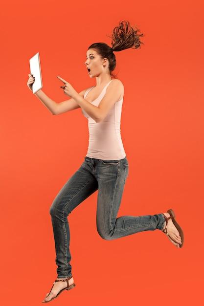 점프하는 동안 노트북 또는 태블릿 가제트를 사용하여 파란색 스튜디오 배경 위에 젊은 여자의 점프. 모션 또는 움직임에서 실행중인 소녀. 무료 사진