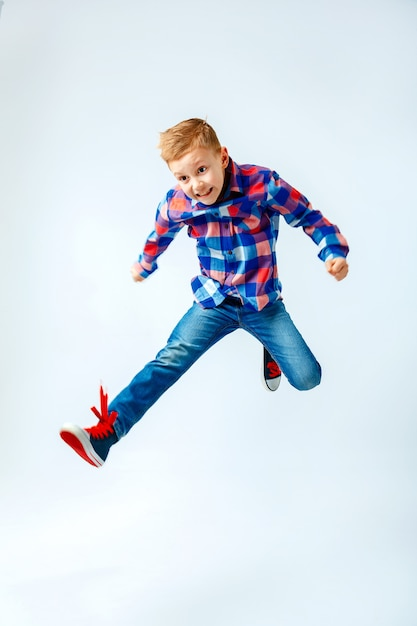 Jumping little boy in the colorful plaid shirt, blue jeans, gumshoes. isolated. Premium Photo