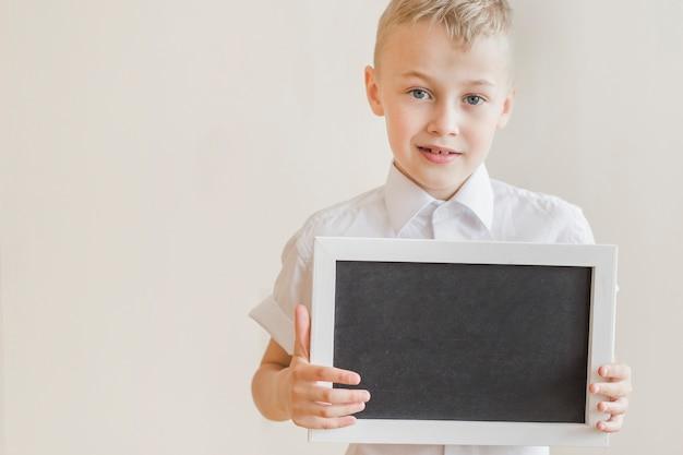 Junior holding chalkboard in studio Free Photo