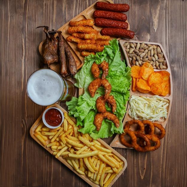 Нездоровые пищевые продукты в деревянных тарелках с пивом, сыром, барбекю, фисташковым сверху Бесплатные Фотографии