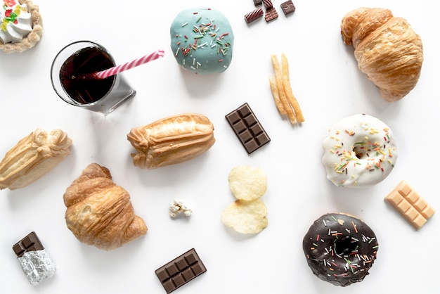 Junk food with chocolate bar and cold drink isolated over white surface Free Photo