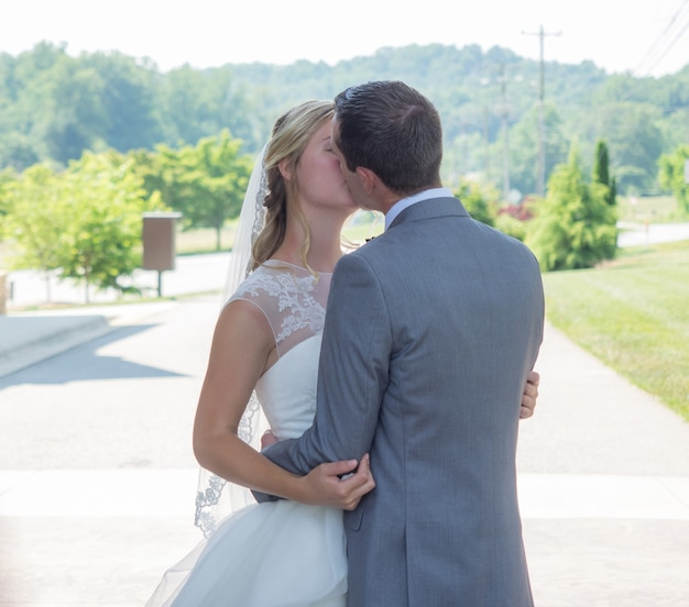 Just-married couple kissing in a garden surrounded by hills and greenery under the sunlight Free Photo