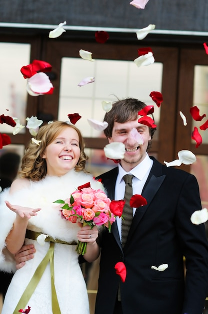 Just married couple under a rain of rose petals Premium Photo